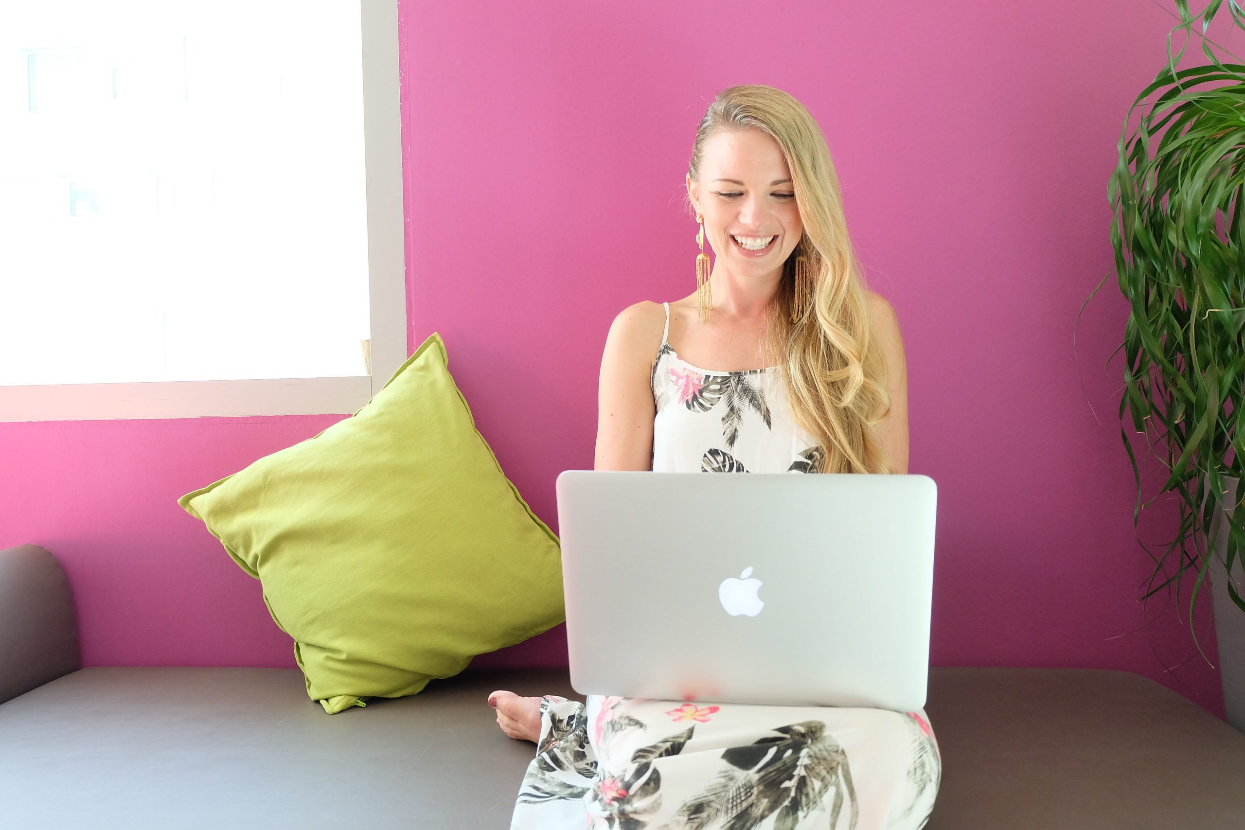 woman sitting at a computer with pink background