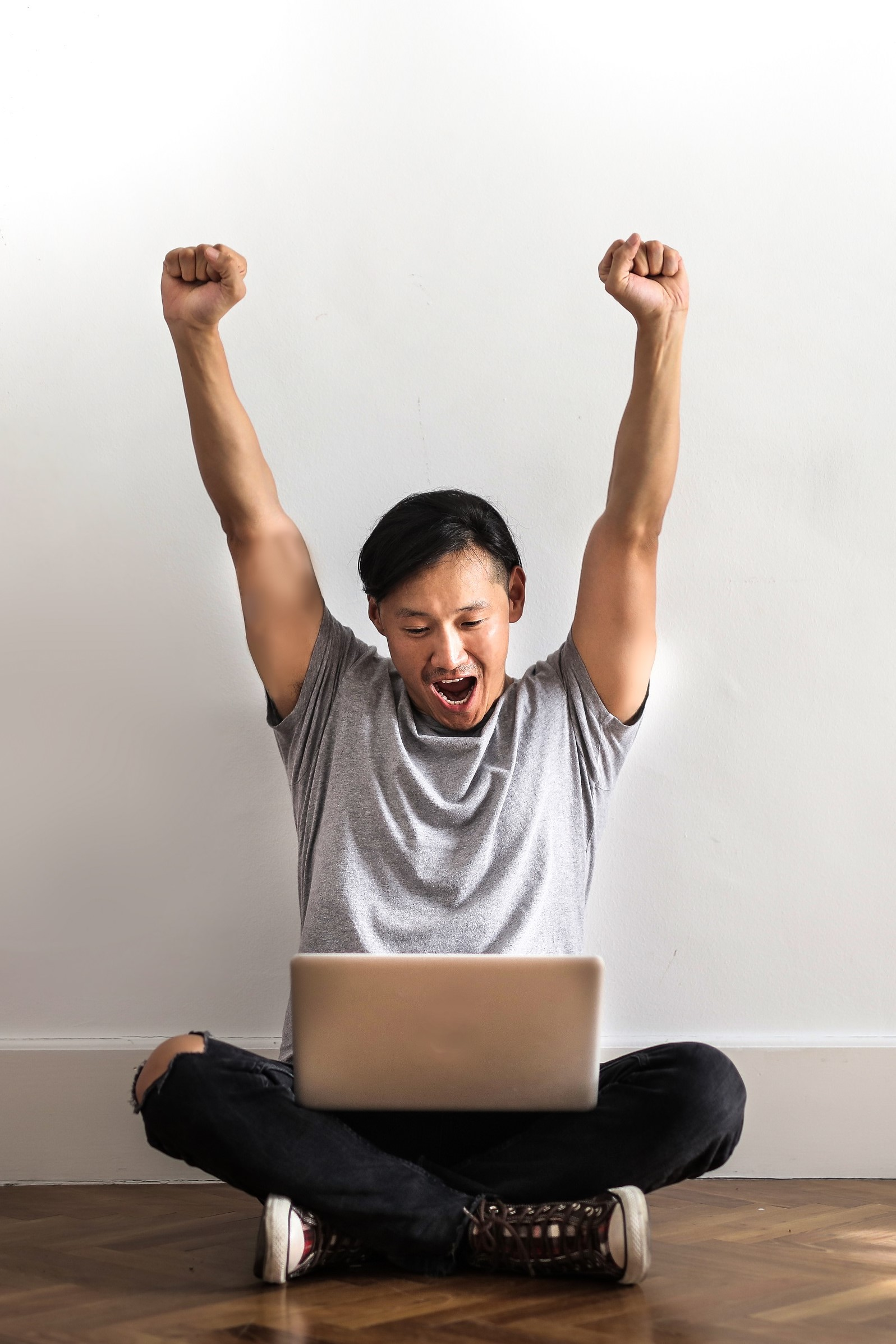 a man in gray t-shirt and black pants sitting on the floor and holding a laptop cheering as he achieved something
