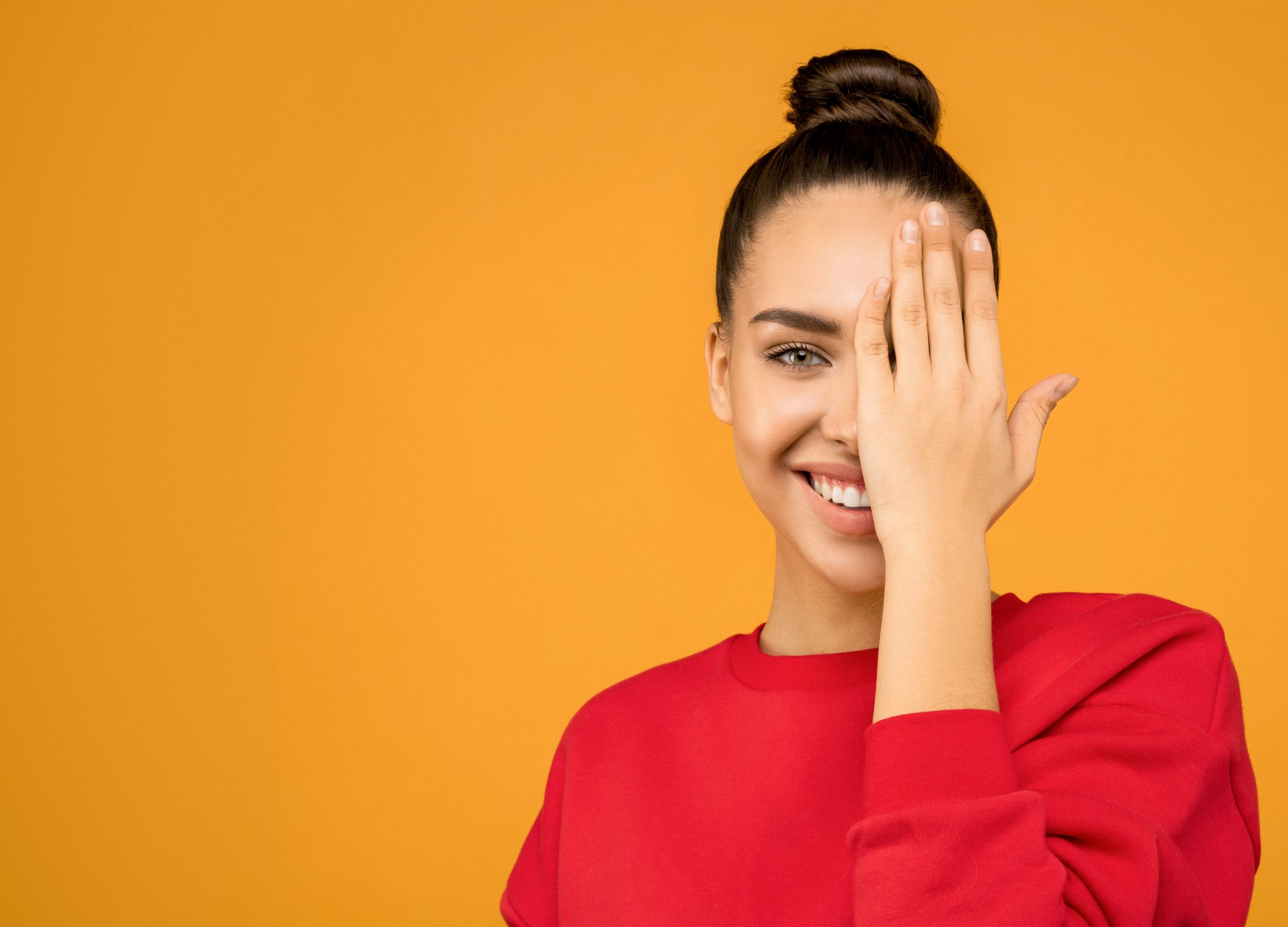 woman wearing a red sweater on orange background