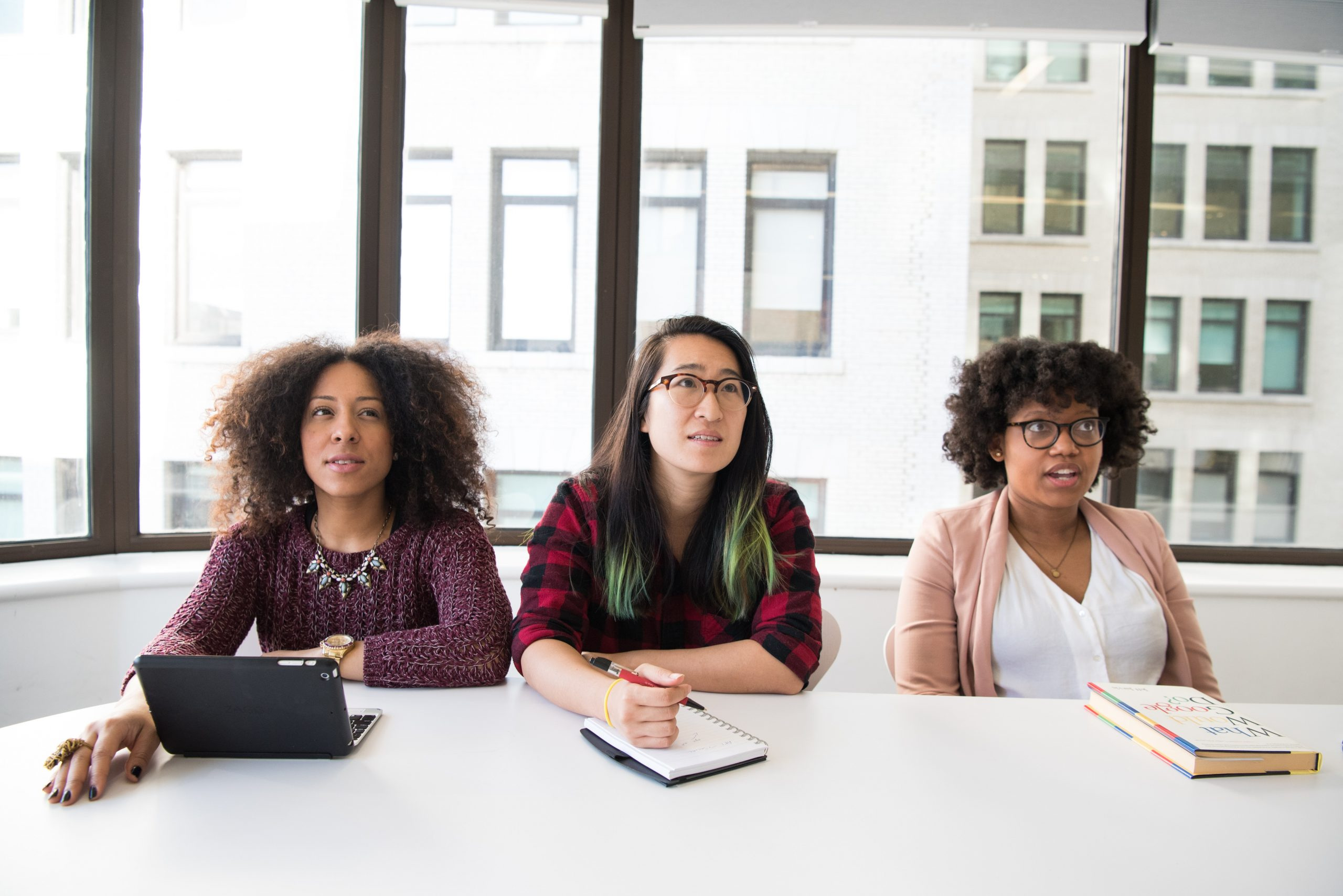three women in an office staring at something