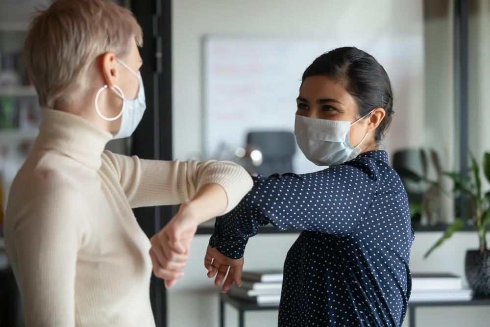 two women wearing masks elbow greeting